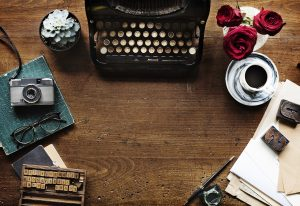 Old-fashioned typewriter with flowers, coffee cup & saucer, glasses, a camera, pencil, paper, and scrabble tiles.
