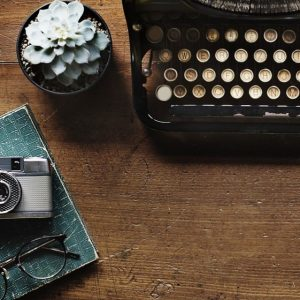 Old-fashioned typewriter with flower in mug and camera on book