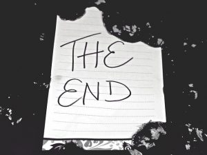 """The End"" written on a ragged piece of notebook paper against a black background"
