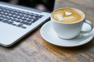Frothy Coffee beside Laptop Keyboard