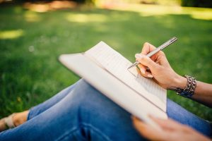 Woman in jeans writing in journal