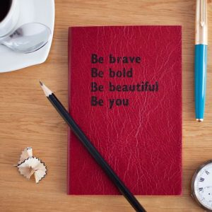"Red book with inspirational quote: ""Be brave. Be bold. Be beautiful. Be you."""